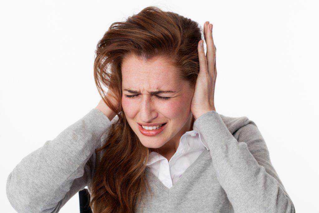 Mujer con acúfenos, tinnitus o ruidos de oídos