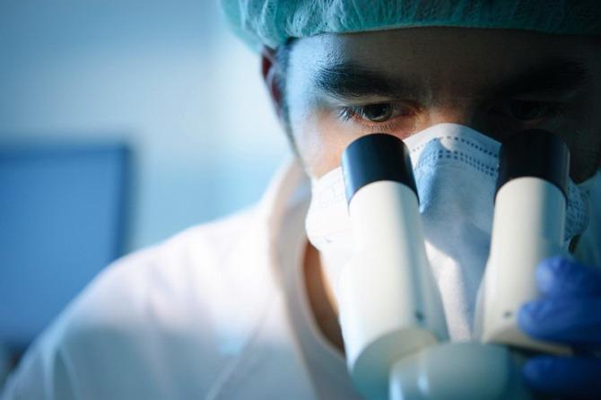 Otorrinolaringólogo realizando exploración microscópica en su consulta